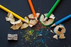 Bleistiftspitzer und farbige Bleistifte Stockfotos
