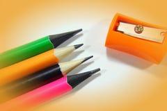Bleistiftspitzer und farbige Bleistifte in einem pil Lizenzfreie Stockbilder