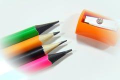 Bleistiftspitzer und farbige Bleistifte in einem Stapel Stockbild