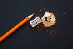 Bleistiftspitzer und orange Bleistift auf Schwarzem Stockbilder