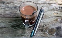Bleistiftstift und -Tasse Kaffee in der hölzernen Tabelle Stockbild