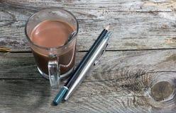 Bleistiftstift und -Tasse Kaffee in der hölzernen Tabelle Stockfotografie