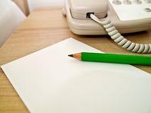 Bleistifttelefon und Anmerkungsauflage Lizenzfreie Stockfotos