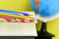 Bleistiftzeichenstifte, -bücher und -Erdkugel Lizenzfreie Stockfotos