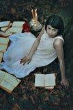 Bleke vrouw en boeken in een donker bos Royalty-vrije Stock Afbeelding