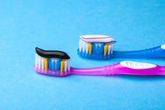 Blekmedeltandkräm är vanlig kulört och svart från kol på tandborsten Begrepp Vilken tandkräm som ska väljas? royaltyfri foto