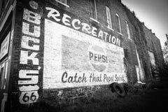 Bleknad gammal tappning målade tecknet på tegelstenväggen på Route 66 Arkivfoton