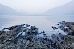 Blekt lugna glödande vatten längs en stenig shoreline på skymning royaltyfri foto