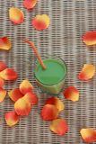 Blended green smoothie and flower petals on table Stock Image