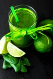 Blended green smoothie with ingredients on black table royalty free stock image