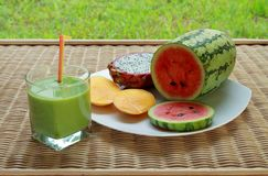 Blended green smoothie and sliced tropical fruits Royalty Free Stock Photos