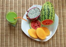 Blended green smoothie and sliced tropical fruits Royalty Free Stock Photography