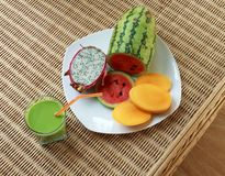 Blended green smoothie and sliced tropical fruits Stock Photography