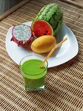 Blended green smoothie and sliced tropical fruits Stock Photos