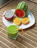 Blended green smoothie and sliced tropical fruits Stock Images