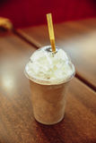 Blended iced coffee with straw on the wooden table.  royalty free stock photos