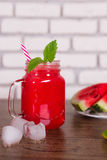 Blended red fruit smoothie in glass jar with straw, ice pieces. Watermelon slices on plate. Selective focus. Harvest Stock Image