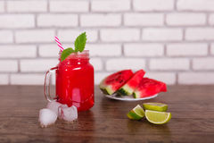Blended red fruit smoothie in glass jar with straw, ice pieces. Watermelon slices on plate. Selective focus. Harvest Royalty Free Stock Image