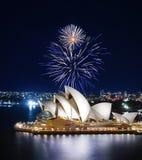 Blendend leuchten blaue und weiße Feuerwerke Sydney Harbor und dem Opernhaus mit glühenden Reflexionen Lizenzfreie Stockfotos