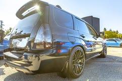 Blendenfleck mit der Sonne, die heraus den Spoiler eines schwarzen Autos w späht Stockfoto