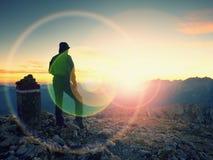 Blendenflecklicht Helle Kreise des Bogens Tourist am Grenzstein auf alpinem Berg Lizenzfreies Stockbild