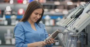 Молодая красивая девушка в голубой рубашке выбирает blender в магазине приборов сток-видео
