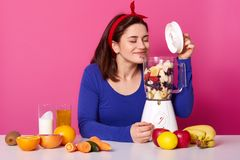Blender with berries and fruit on table. Female makes tasty smoothie and likes its smell. Charming girl wears blue sweater and. Hair band poses against pink stock image