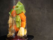 Blender with fresh vegetables. Sliced celery, apple and carrot in a blender cup for a smoothie. Healthy food. raw food. Gray stock image