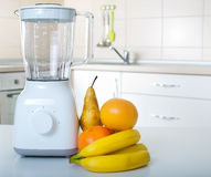 Blender with fruits in kitchen. White blender standing on tabel in kitchen with fresh fruits royalty free stock photo