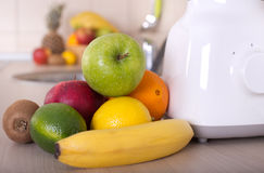 Blender with group of fruits. Preparing smoothie in white blender with different fresh fruits on kitchen countertop. Healthy eating concept Stock Image