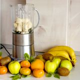 Blender and a lot of fruit on the kitchen table royalty free stock photography
