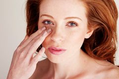 Blending Foundation With Fingertips. Attractive redhead woman in beauty portrait blending foundation on to her face with her fingertips Royalty Free Stock Photography