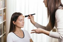 Blending liquid face powder foundation. Make up artist applying liquid face powder foundation to a female client`s face and blending contours royalty free stock photography
