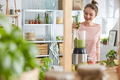 Blending smoothie ingredients. Woman blending healthy fresh ingredients for a green smoothie royalty free stock image