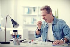 Unhappy ill man sneezing. Bless you. Unhappy nice ill man sitting in his office and holding a paper tissue while sneezing Stock Photo