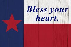 Bless your heart saying with the Texas state flag. On weathered wood stock photography