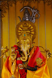 Blessed brass Ganesha close up. Elephant god statue in front of the gold Royalty Free Stock Images