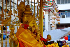 Blessed brass Ganesha close up. Elephant god statue in front of the gold Stock Image