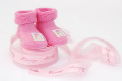 Blessed with little girl!. Little pink socks on the pink ribbon Royalty Free Stock Images