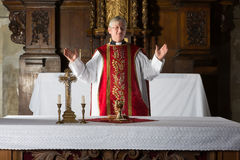 Blessing the chalice. Christian priest blessing the hosts and chalice in a 17th century church interior stock images