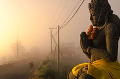 Blessing. Child going to school in the mist at sunrise in front of the mount Batur, in Kintamani, Bali Stock Photo