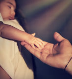 Blessing of God. Closeup photo of cute little baby on mothers hands touching fatherd hand, bright sun rays shining on their, blessing of God, hope and rescue stock image