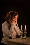 Blessing over Candles. Jewish woman says blessing upon lighting candles, covering eyes in traditional manner Royalty Free Stock Photography