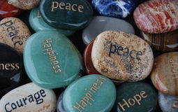 Blessing Stones, Hope, Courage, Happiness. Colorful smooth polished rocks with words happiness, courage, peace and hope printed on them Royalty Free Stock Image