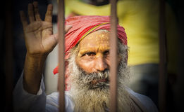 The Blessings of a Sadhu (holy man) captured through iron railin. New Delhi, India - February 6, 2016: Portrait of an unknown Sadhu (holy man) with intriguing Royalty Free Stock Photos