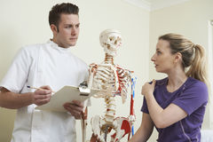 Blessure à l'épaule de description patiente femelle à l'ostéopathe Images libres de droits