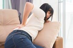 Blessure douloureuse de femme plus lombo-sacrée dans le salon Photos stock