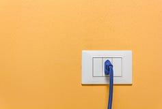 Bleu branchez une prise murale sur un mur orange Images stock