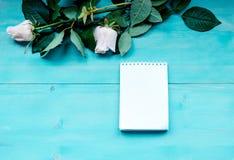 Bleu de disposition de fond de ressort sur le fond en bois bleu avec des fleurs des roses bloc-notes et feuilles pour des disques Photos libres de droits