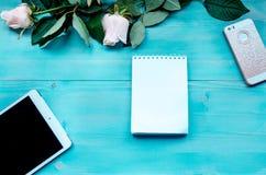 Bleu de disposition de fond de ressort sur le fond en bois bleu avec des fleurs des roses bloc-notes et feuilles pour des disques Image libre de droits